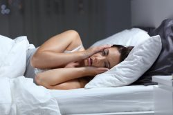Woman in bed, thinking about importance of sleep in Melbourne