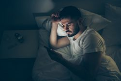 Man in bed with phone, cell phone causing sleep loss