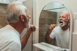 Man brushing teeth as part of cleaning oral appliance in Jupiter