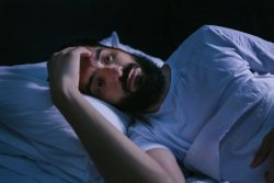 Man in bed, struggling with anxiety and sleep apnea in Boca Raton